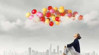Frau schaut mit positiven Gedanken auf Luftballons