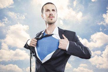 Young businessman acting like a super hero and tearing his shirt off