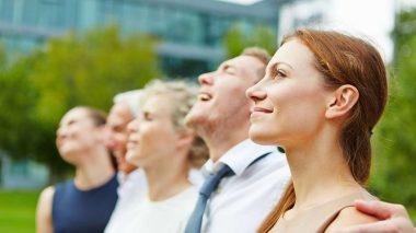 Geschäftsfrau mit Business Team im Freien schaut gemeinsam in eine Richtung