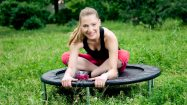 Relaxed woman sitting on mini trampoline