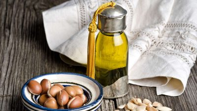 Bottle of argan oil and argan fruit. Argan oil is used for skincare products.