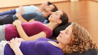 Gruppe entspannt gemeinsam im Liegen im Sportstudio