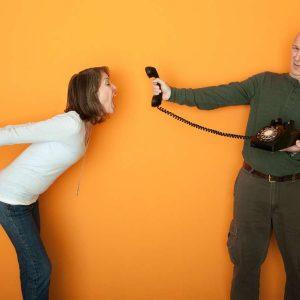 Gestresste Frau schreit in Telefonhörer