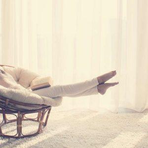 Gelassene Frau streckt sich in Stuhl