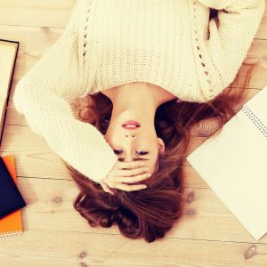Gelassenheit lernen: Frau liegt gestresst auf dem Boden