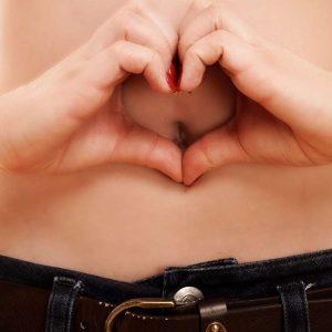 Frau zeigt ein Herz vor dem Bauch - Schlank durch gute Darmbakterien