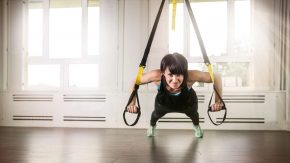 Eine Frau trainiert mit dem TRX
