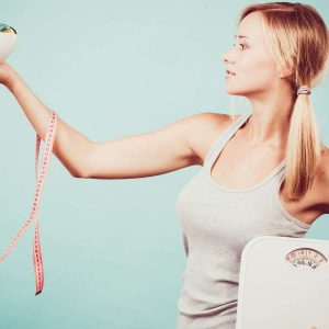 Junge Frau mit Waage und Maßband - 10 erfolgreiche Diäten