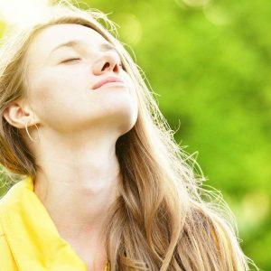 Frau macht Atemübungen für achtsames Atmen