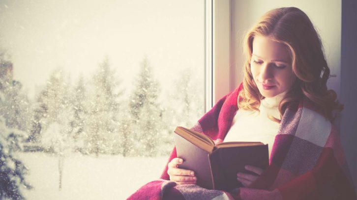 Glückliche Frau liest ein gutes Buch im Winter