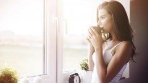 Eine Frau trinkt ein heißes Getränk zum Wachwerden am Morgen