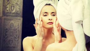 Frau pflegt ihre Haut vor dem Spiegel - Schöne Haut ab 30