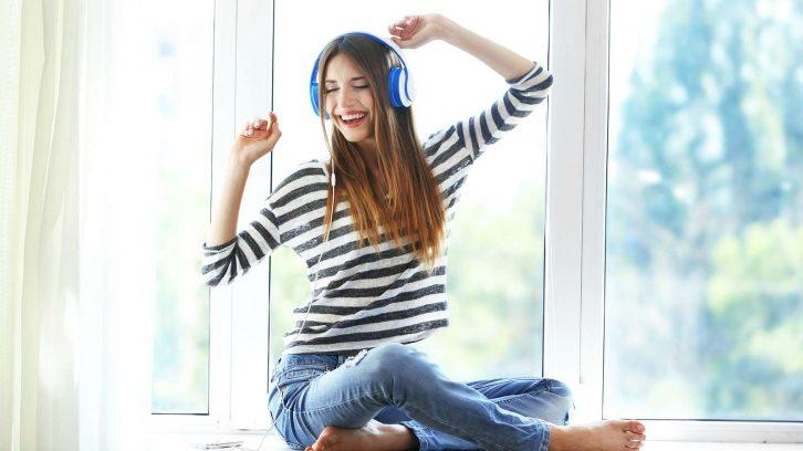 Eine junge Frau hört Musik, singt und ist glücklich