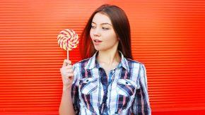 Frau mit Süßem: Anzeichen, dass du zu viel Zucker isst