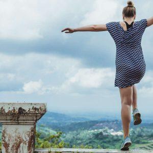 Junge Frau springt frei und leidenschaftlich über eine Mauer