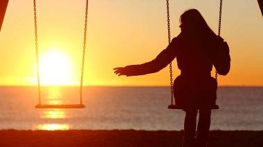 Frau auf Schaukel vermisst ihren Freund, der per Ghosting Schluss gemacht hat