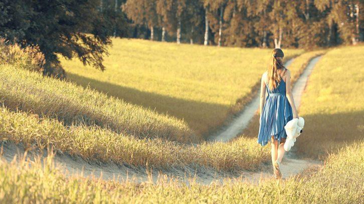 Frau läuft im Sommer über einen Feldweg und lässt alle Selbsttäuschungen hinter sich