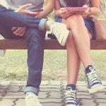 Mann und Frau nutzen ein Smartphone statt zu reden: Smartphone-Sucht